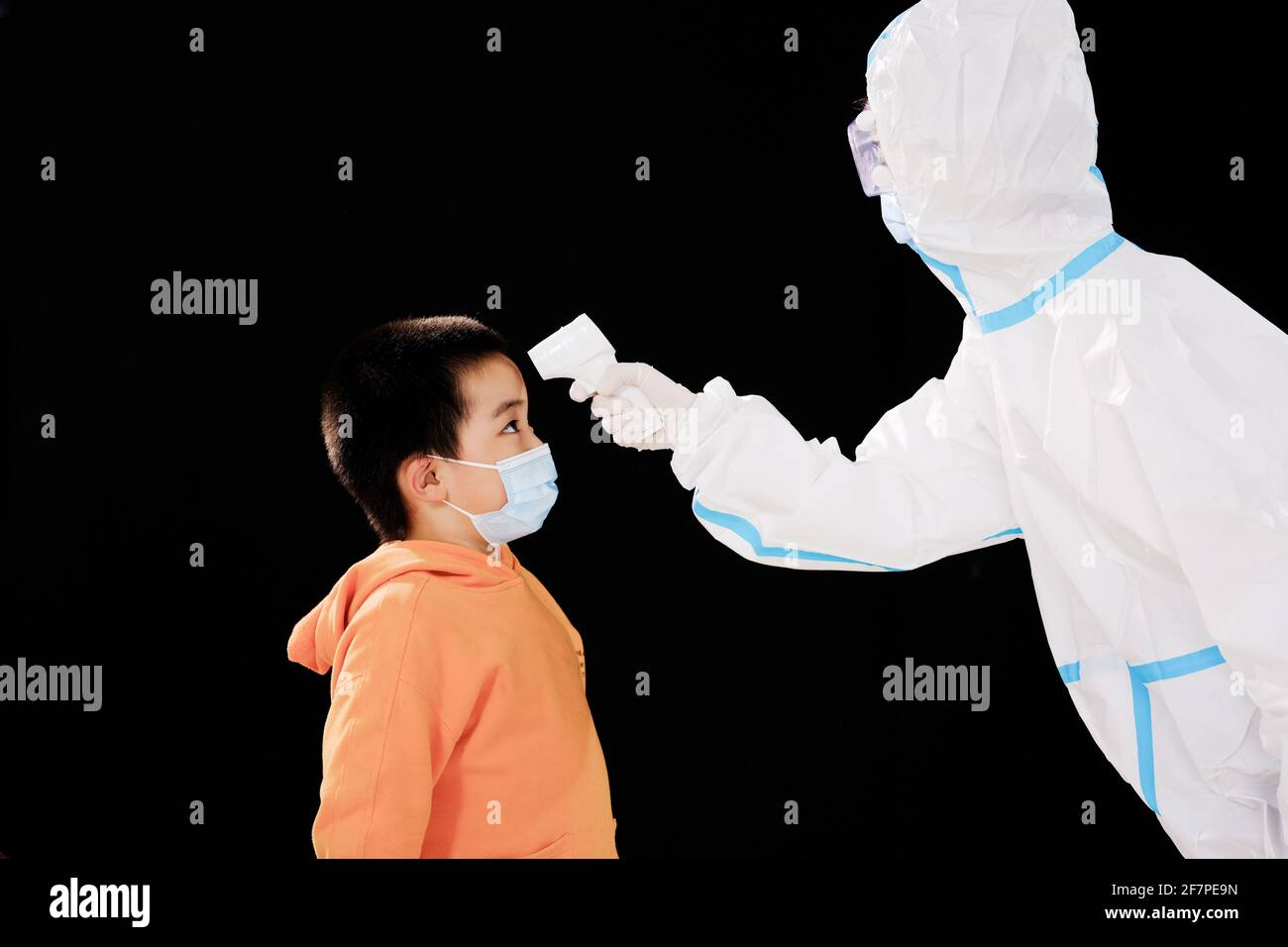 La femme médecin en vêtements de protection médicale a pris le garçon température face à face Banque D'Images