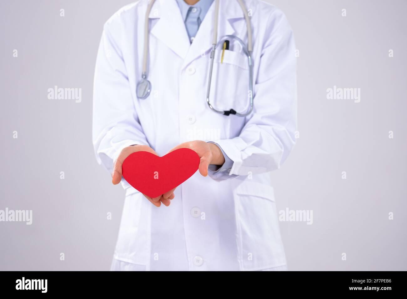 Une jeune femme médecin avec un masque a un rouge gros plan du cœur Banque D'Images