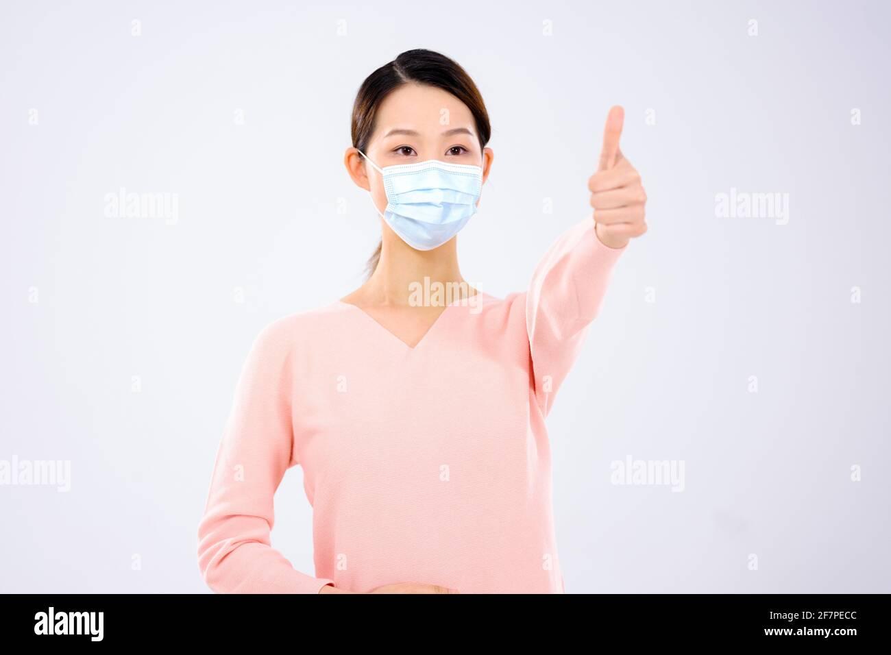 Une jeune femme avec un masque a tenu son pouce sourire Banque D'Images