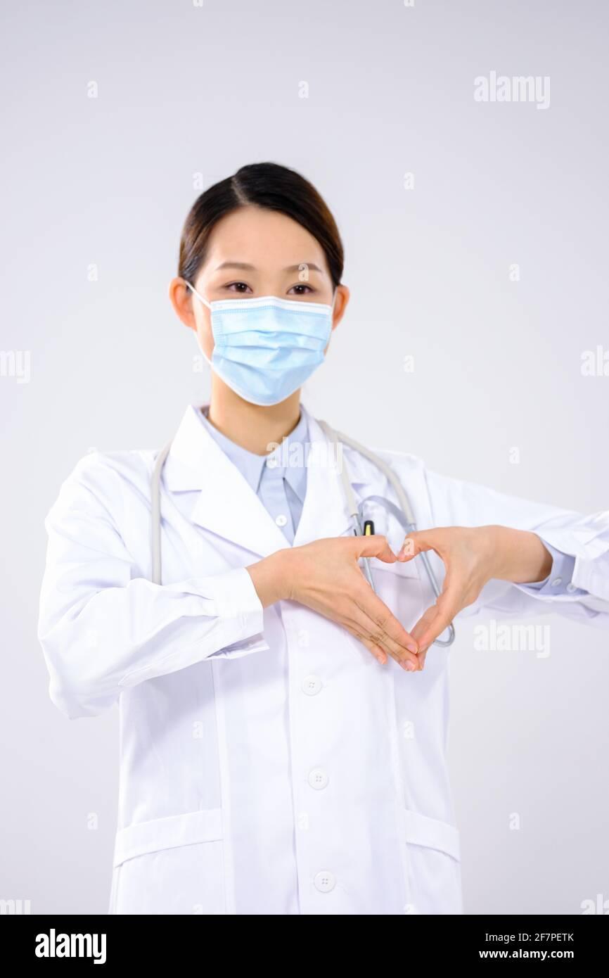 Bixin, une jeune femme médecin portant un masque regardant la caméra Banque D'Images