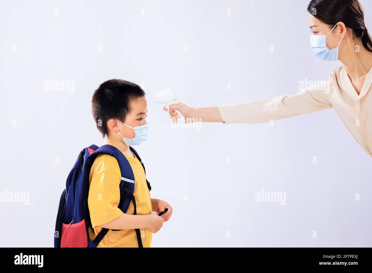 Le petit garçon a pris sa température avant l'école par son maman Banque D'Images