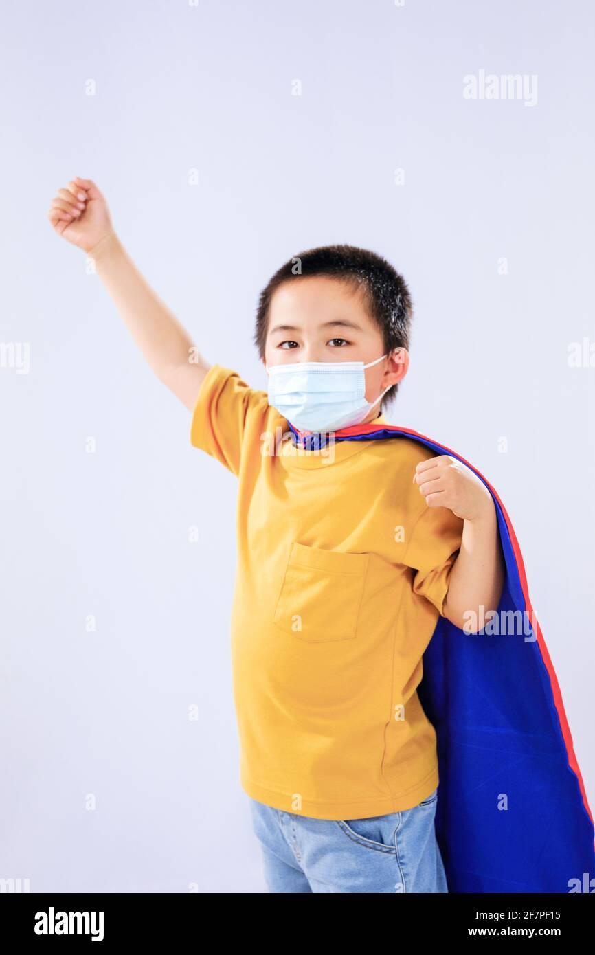 Le petit garçon dans le masque portait un super-homme costume Banque D'Images