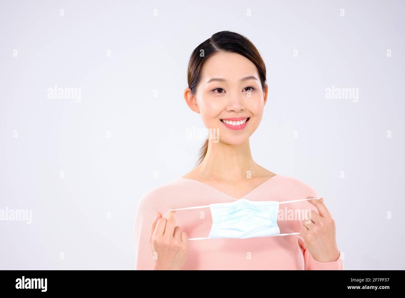 Une jeune femme a pris son masque en souriant Banque D'Images