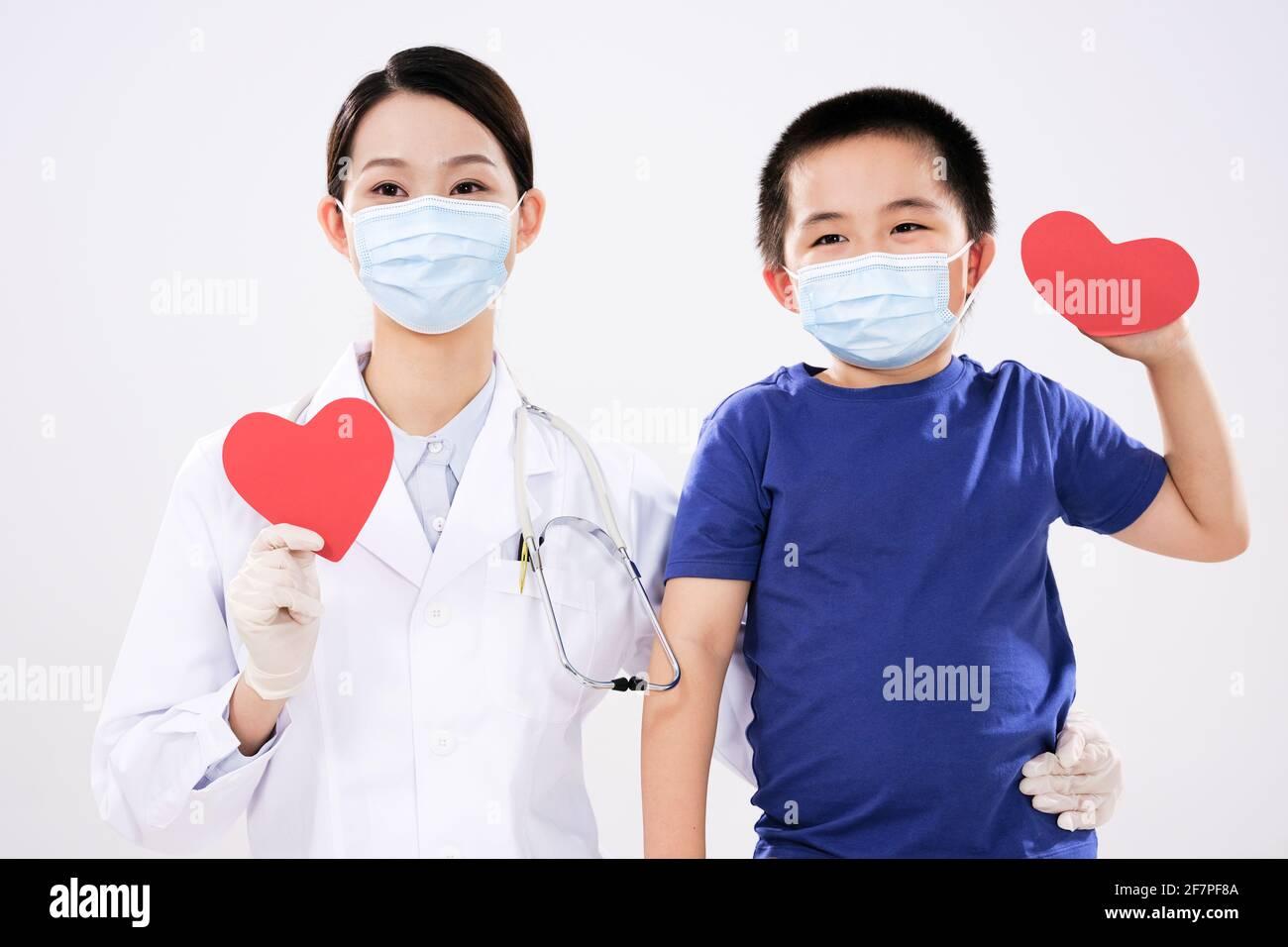 Une femme médecin et un petit garçon avaient chacun un cœur rouge regardant la caméra Banque D'Images