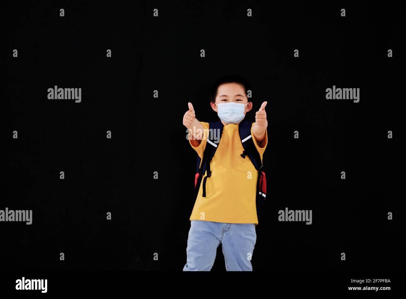 Un petit garçon avec un masque a tenu son pouce debout Banque D'Images