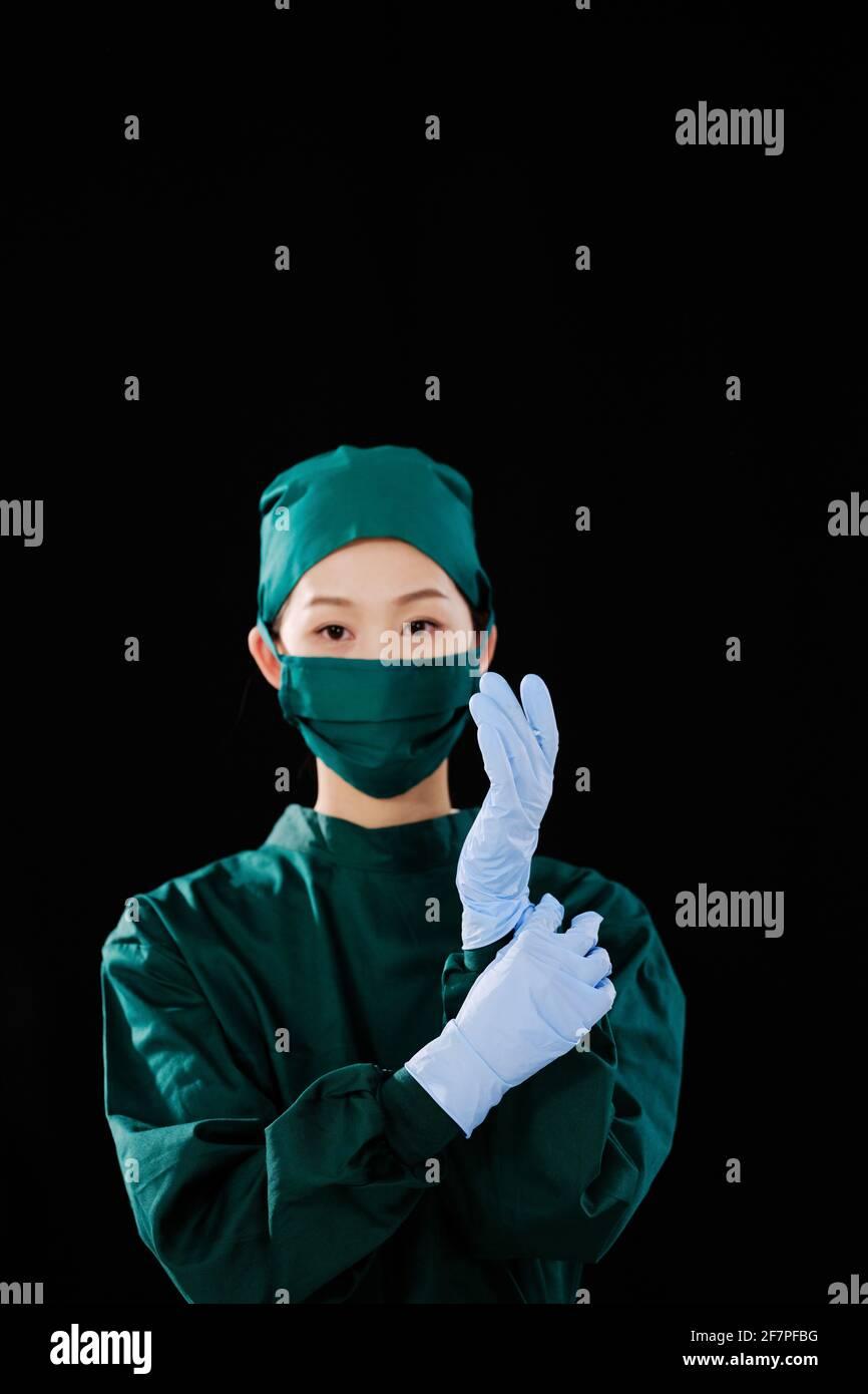 Une jeune femme chirurgien portait des gants chirurgicaux en regardant le appareil photo Banque D'Images