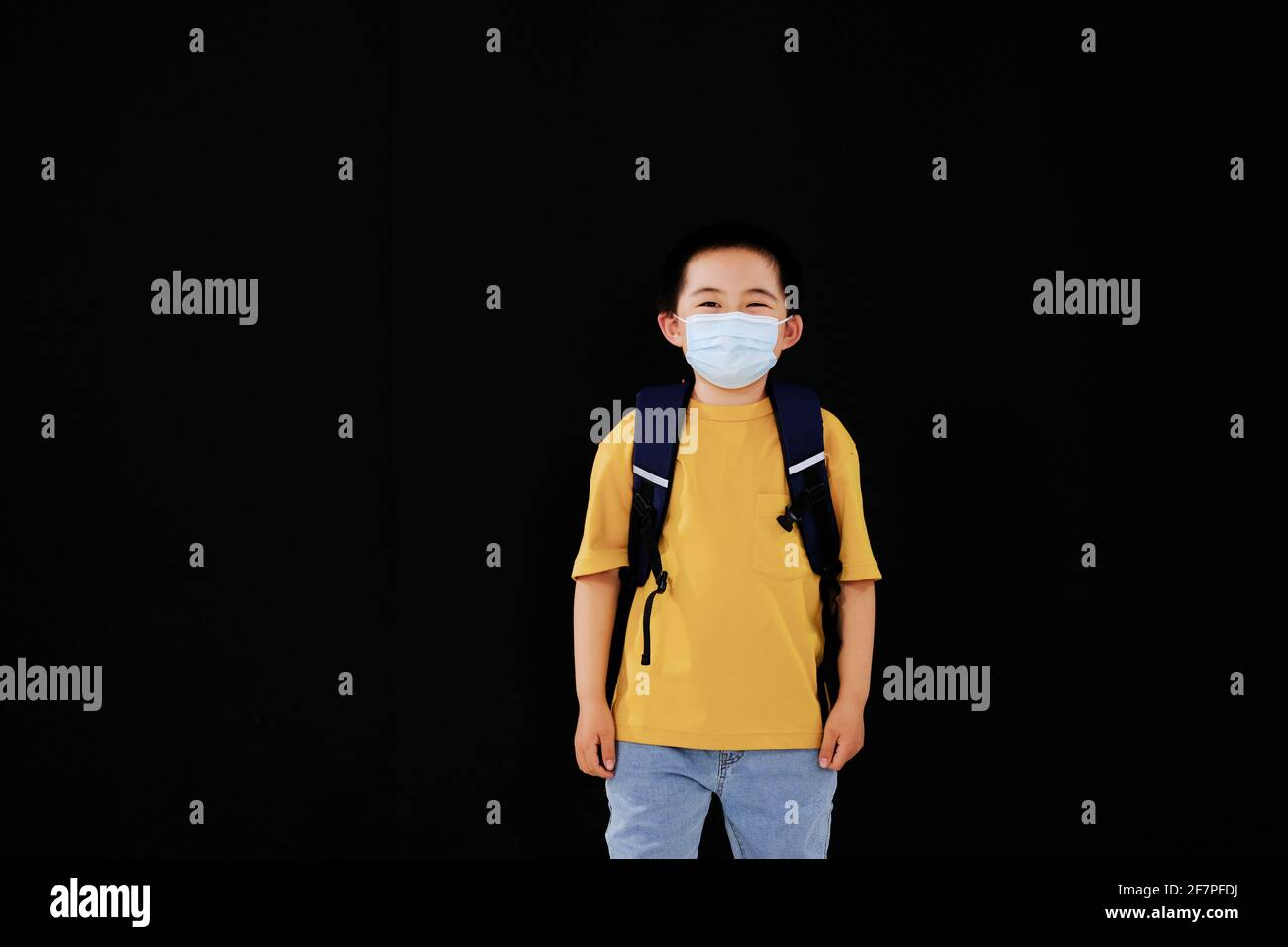 Le petit garçon avec masque va à l'école debout Banque D'Images