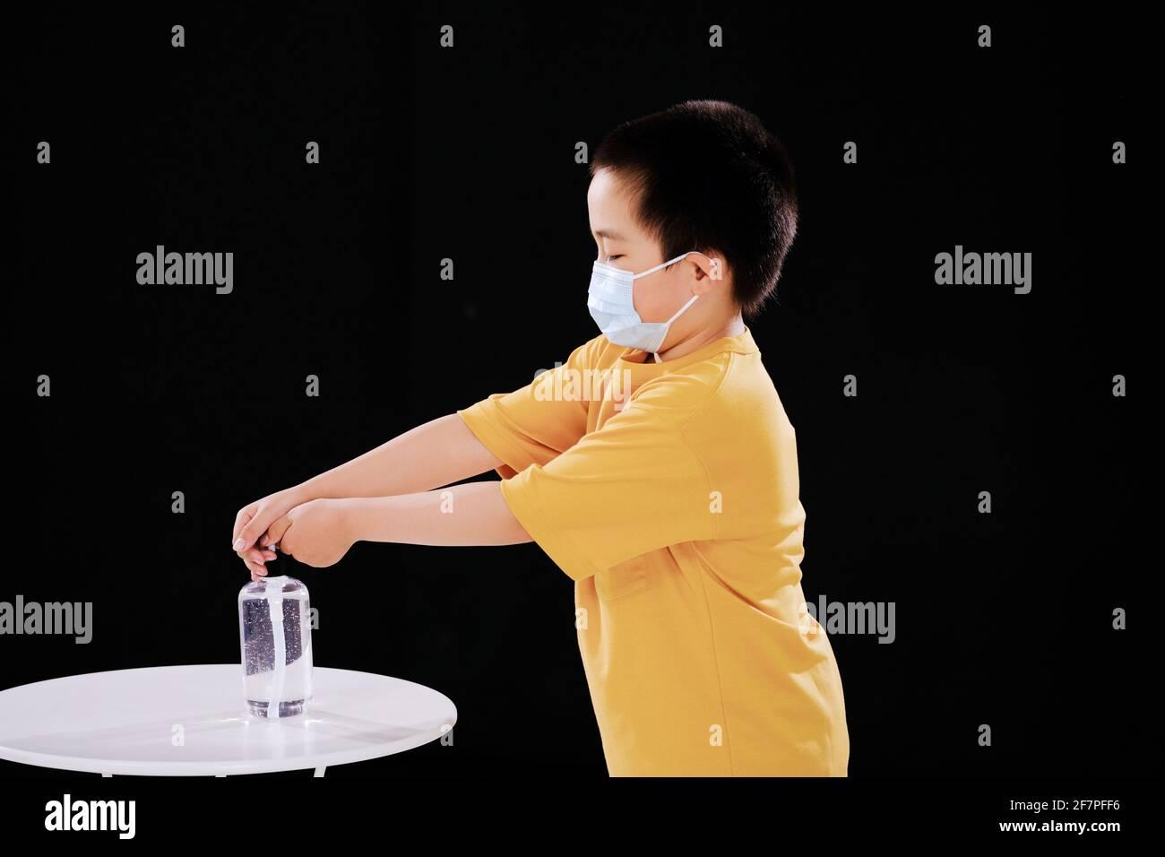 Un petit garçon avec un masque utilise un désinfectant pour les mains Banque D'Images