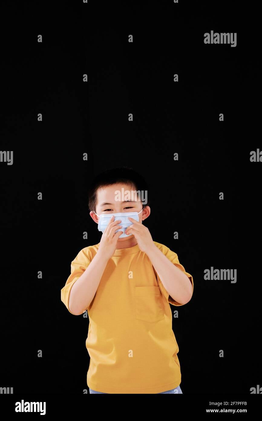 Un petit garçon portait un masque en regardant le appareil photo Banque D'Images