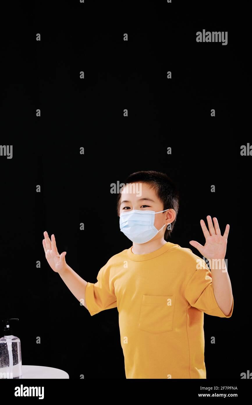 Le petit garçon avec masque montre ses mains après utilisation désinfectant pour les mains avec joie Banque D'Images