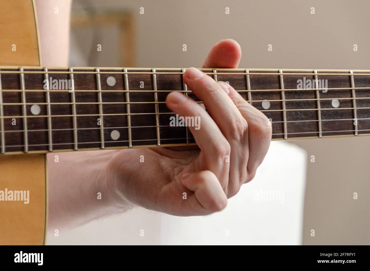 gros plan sur les doigts de sexe masculin jouant des cordes de guitare acoustique Banque D'Images