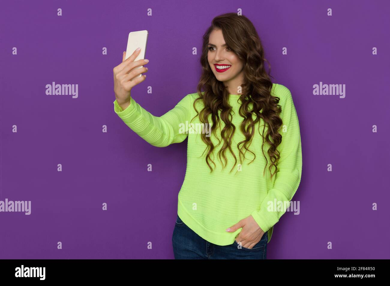 Belle jeune femme en vert fluo chandail tient le téléphone, prend un selfie et sourire. Taille haute, prise en studio sur fond violet. Banque D'Images
