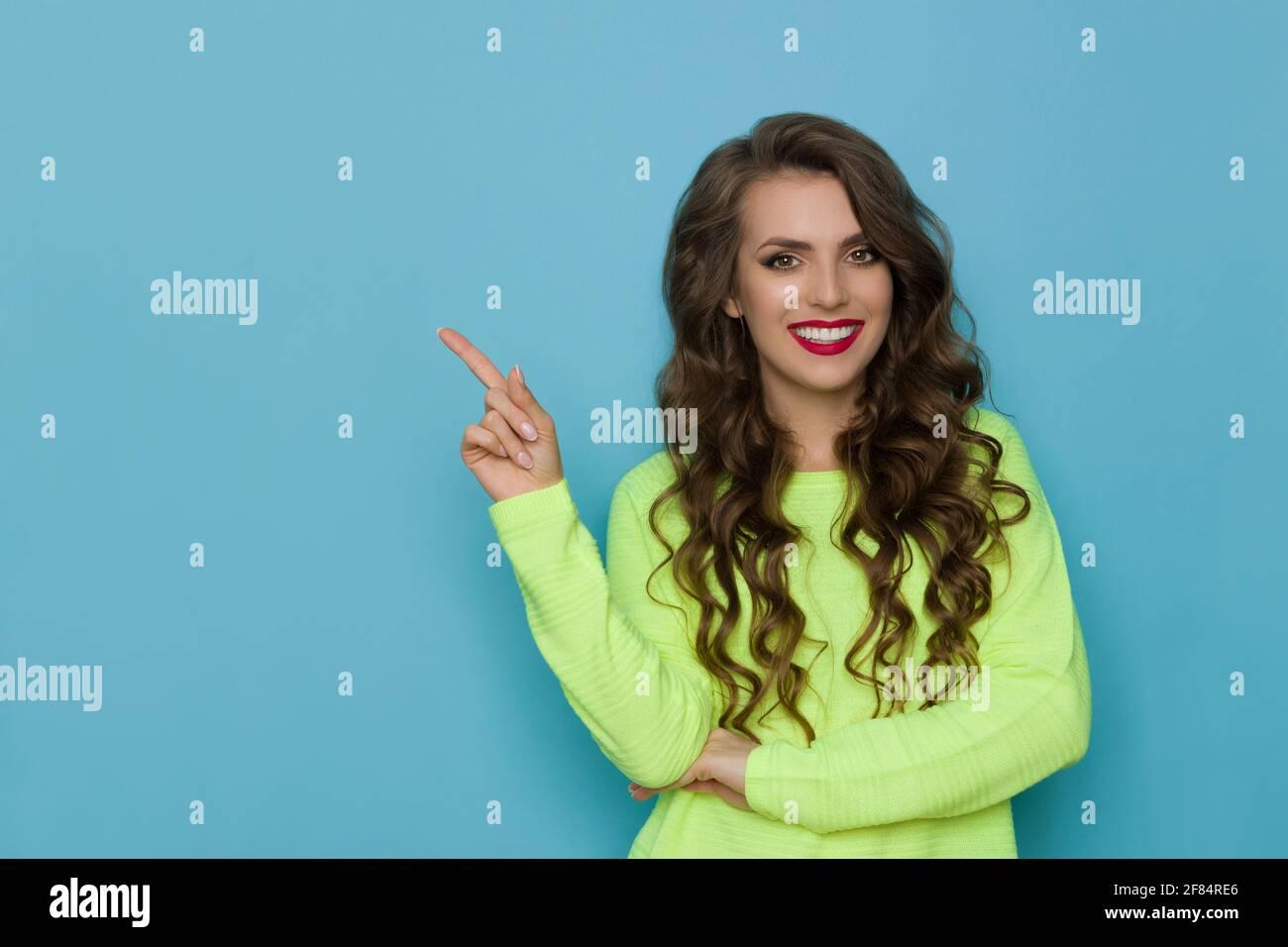 Belle jeune femme souriante dans le chandail de citron vert de néon est pointant vers le haut. Vue avant. Taille haute studio tourné sur fond bleu. Banque D'Images