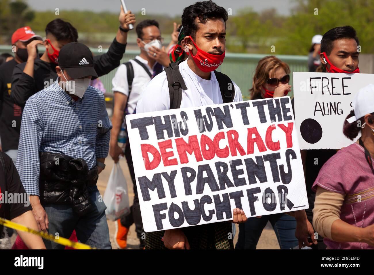 Un jeune homme porte un signe faisant référence aux sacrifices de ses parents pour la démocratie lors d'une marche contre le coup d'État en Birmanie. Banque D'Images