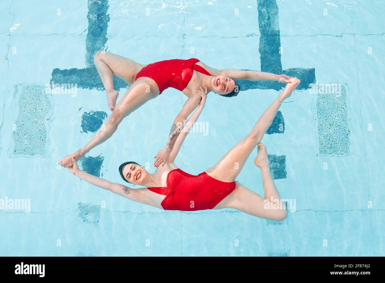 Rebecca Richardson (en haut) et Geneviève Florence, membres de l'équipe de natation synchronisée Aquabatix lors d'une séance d'entraînement dans la piscine du Clissold Leisure Centre, au nord de Londres, qui a rouvert au public alors que l'Angleterre fait un nouveau pas vers la normalité avec l'assouplissement supplémentaire des restrictions de verrouillage. Date de la photo: Lundi 12 avril 2021. Banque D'Images