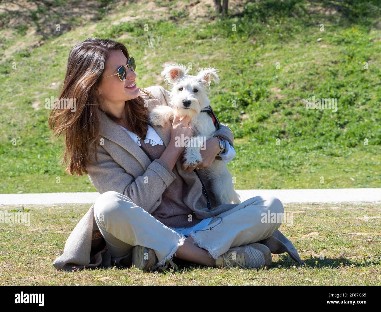 Jeune femme assise sur le terrain, passant du temps avec son chiot schnauzer blanc. Banque D'Images