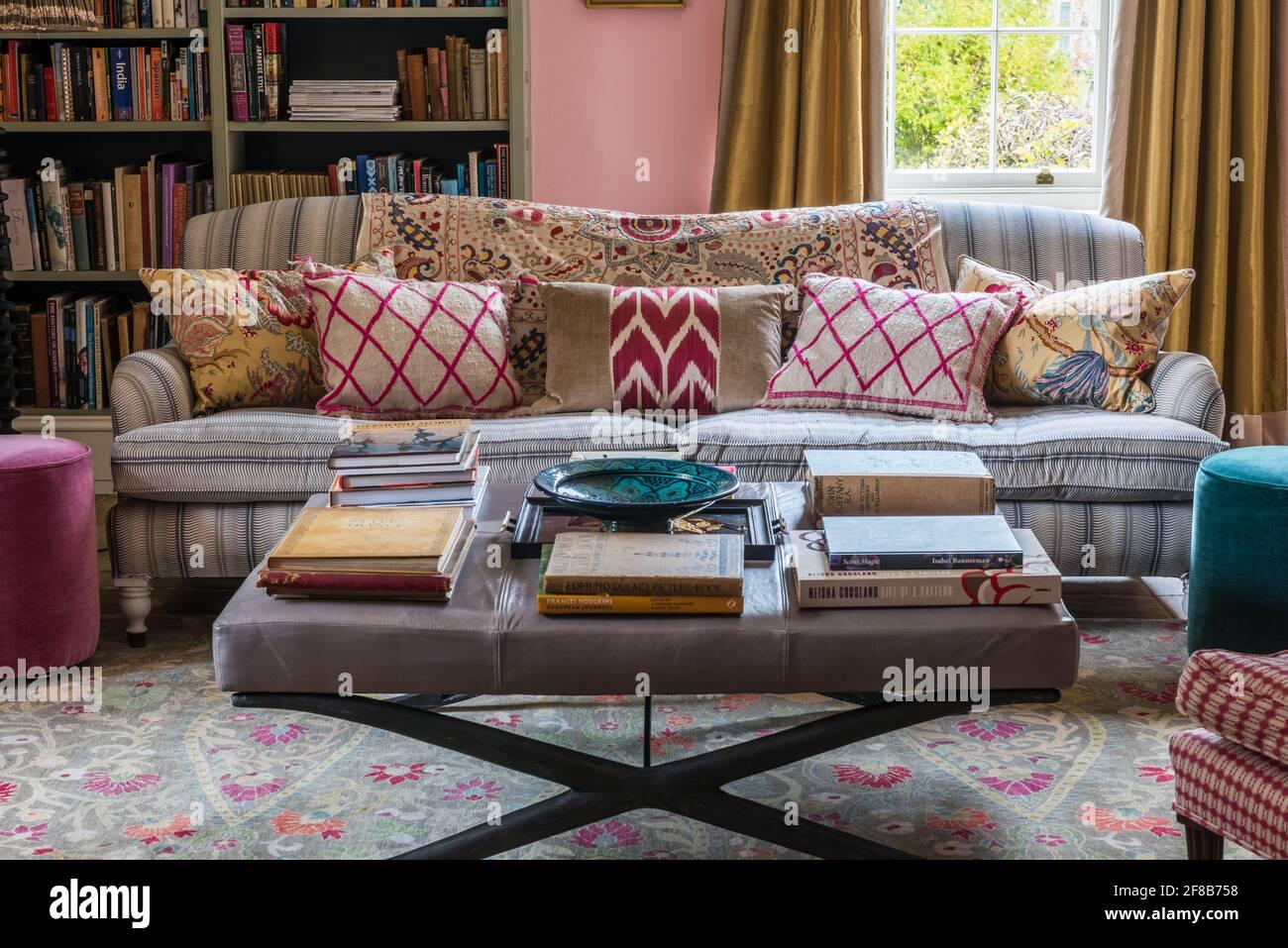 Livres sur pouf avec canapé George Smith dans la salle de séjour De la ferme Suffolk Banque D'Images