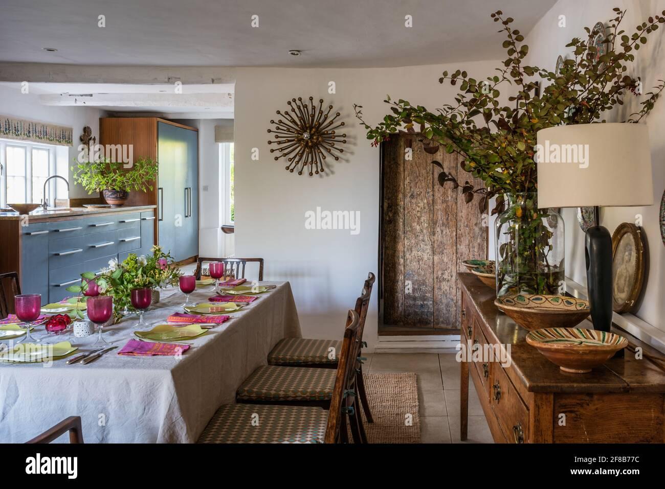 """Table pour huit avec des murs en """"blanc propre"""" et vue sur la cuisine dans la ferme Suffolk classée Grade II modernisée. Banque D'Images"""