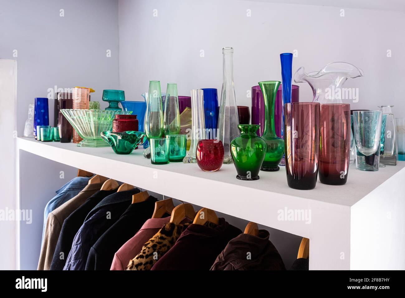 Collection de verre sur étagère au-dessus des manteaux, un bijou-comme l'étalage. Banque D'Images