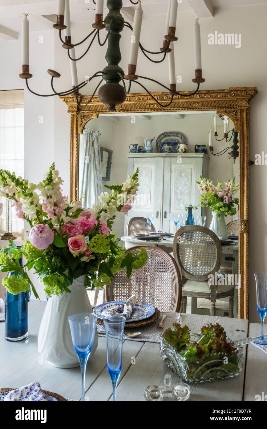 Miroir à cadre doré géorgien avec verrerie sur table à manger dans le West Sussex Coastal renovation. Banque D'Images