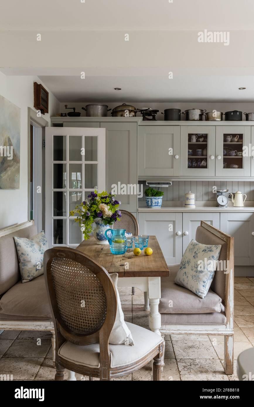 Cuisine de style Shaker avec bancs Gustavian et sol travertin dans les années 1930 West Sussex rénovation côtière. Banque D'Images