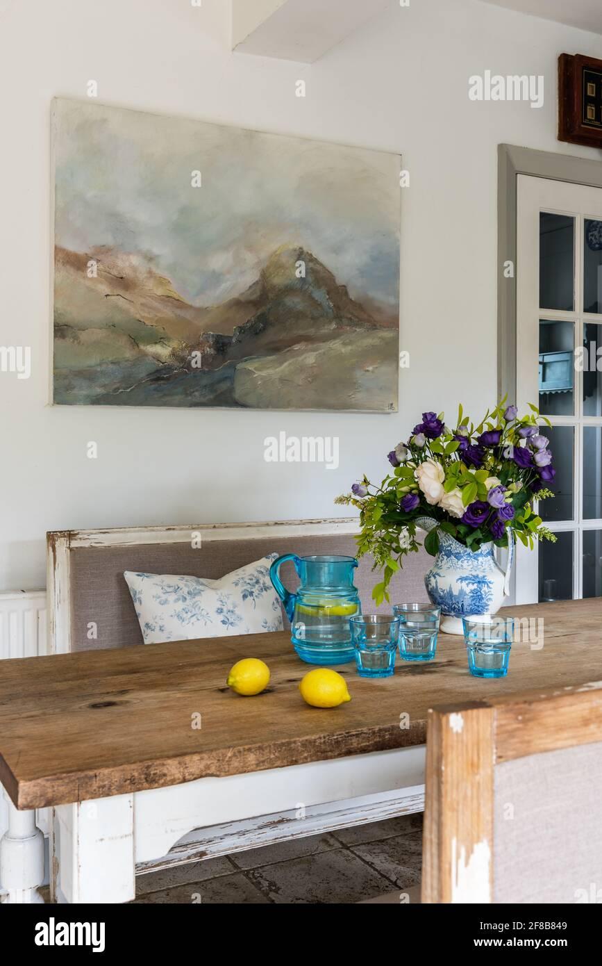 Œuvre de Sue Green au-dessus de la table avec des bancs Gustavian dans West Sussex cuisine repensée. Banque D'Images