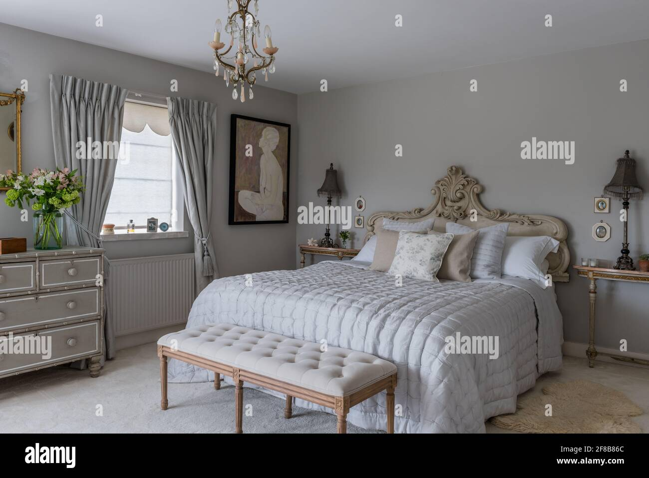Tête de lit en mousseline avec murs dans la salle des lampes grise dans la chambre côtière du West Sussex. Banque D'Images