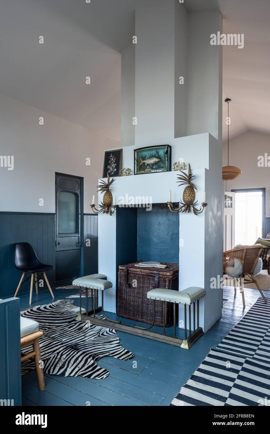 Tapis de chemin de table à rayures et peau de zèbre avec appliques à l'ananas et peinture en descente dans une maison de vacances rénovée, West Sussex Banque D'Images