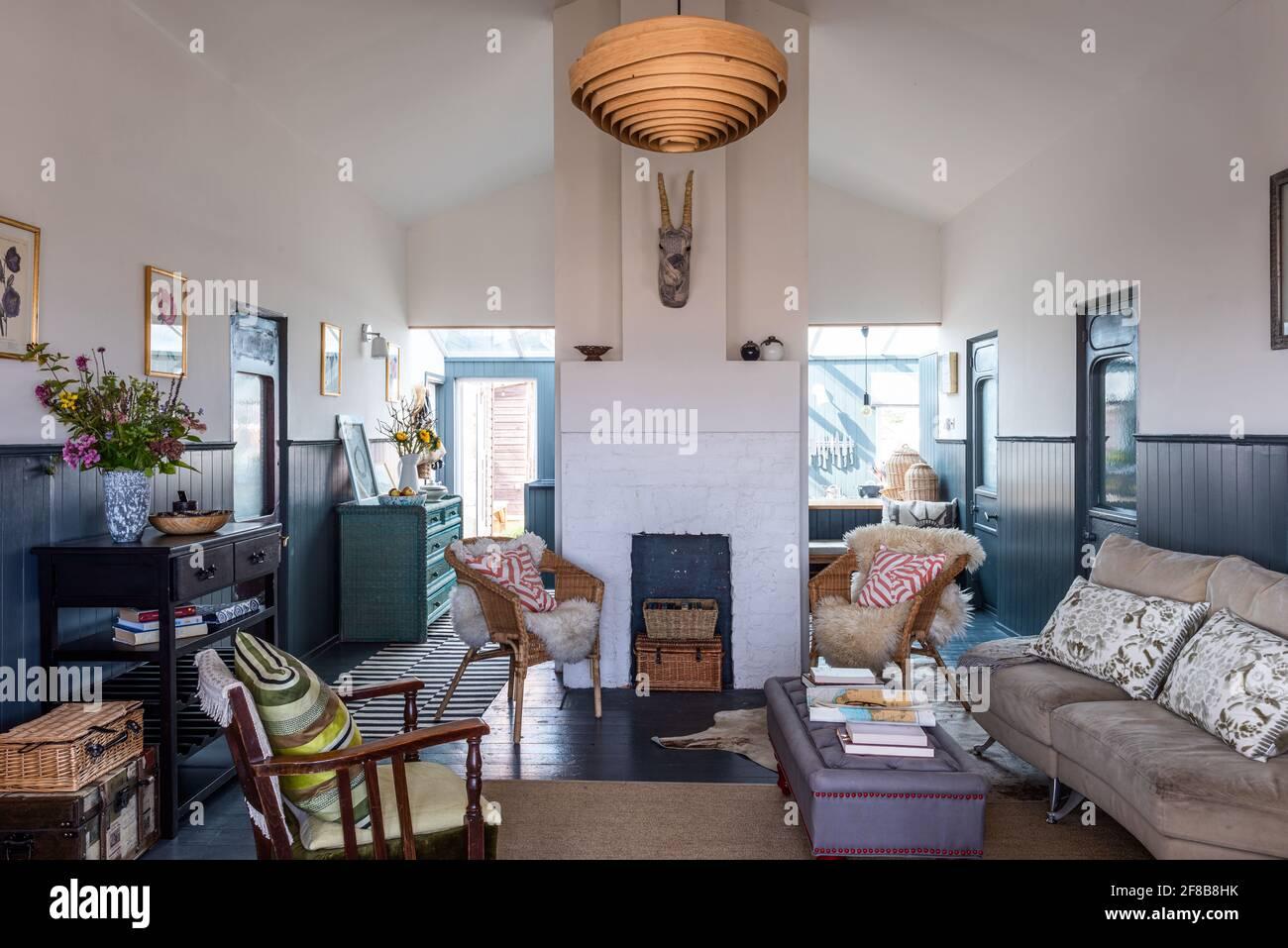 Coussins de la Guilde des designers, chaises en osier avec jetés en peau de mouton et lampe en bois spiralé de la Guilde des designers dans la maison de vacances rénovée de West Sussex. Banque D'Images