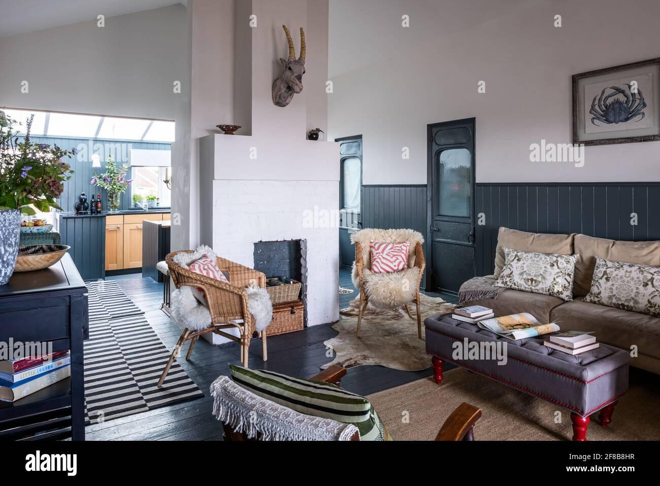 Chaises en osier et jetés en peau de mouton avec lampe en bois spiralé de la Guilde des designers dans la maison de vacances rénovée de West Sussex. Banque D'Images