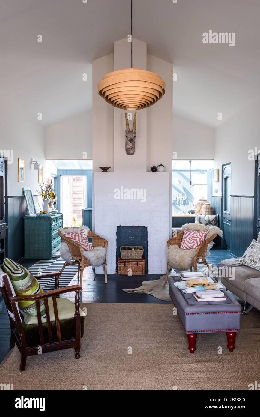 Chaises en osier avec jetés en peau de mouton et lampe en bois spiralé de la Guilde des designers dans la maison de vacances rénovée de West Sussex. Banque D'Images