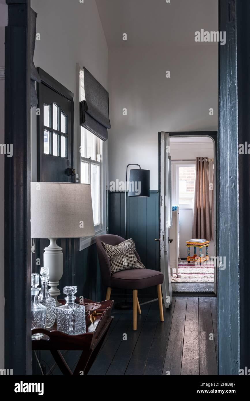 Decanters sur la table latérale avec chaise et dado en descente, West Sussex maison de vacances rénovation. Banque D'Images