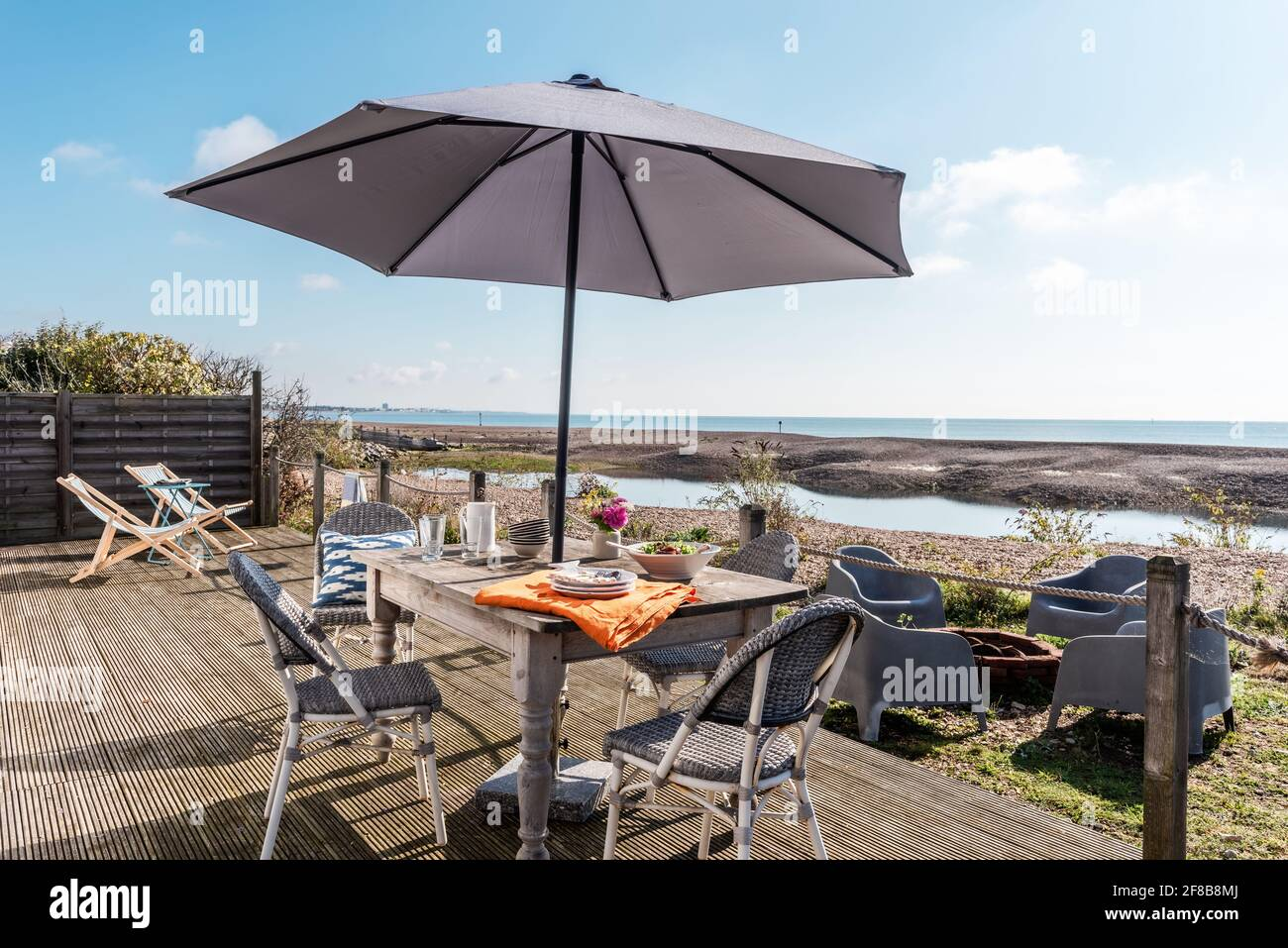 Paarasol ombre table et chaises sur la terrasse de West Sussex maison de vacances. Banque D'Images