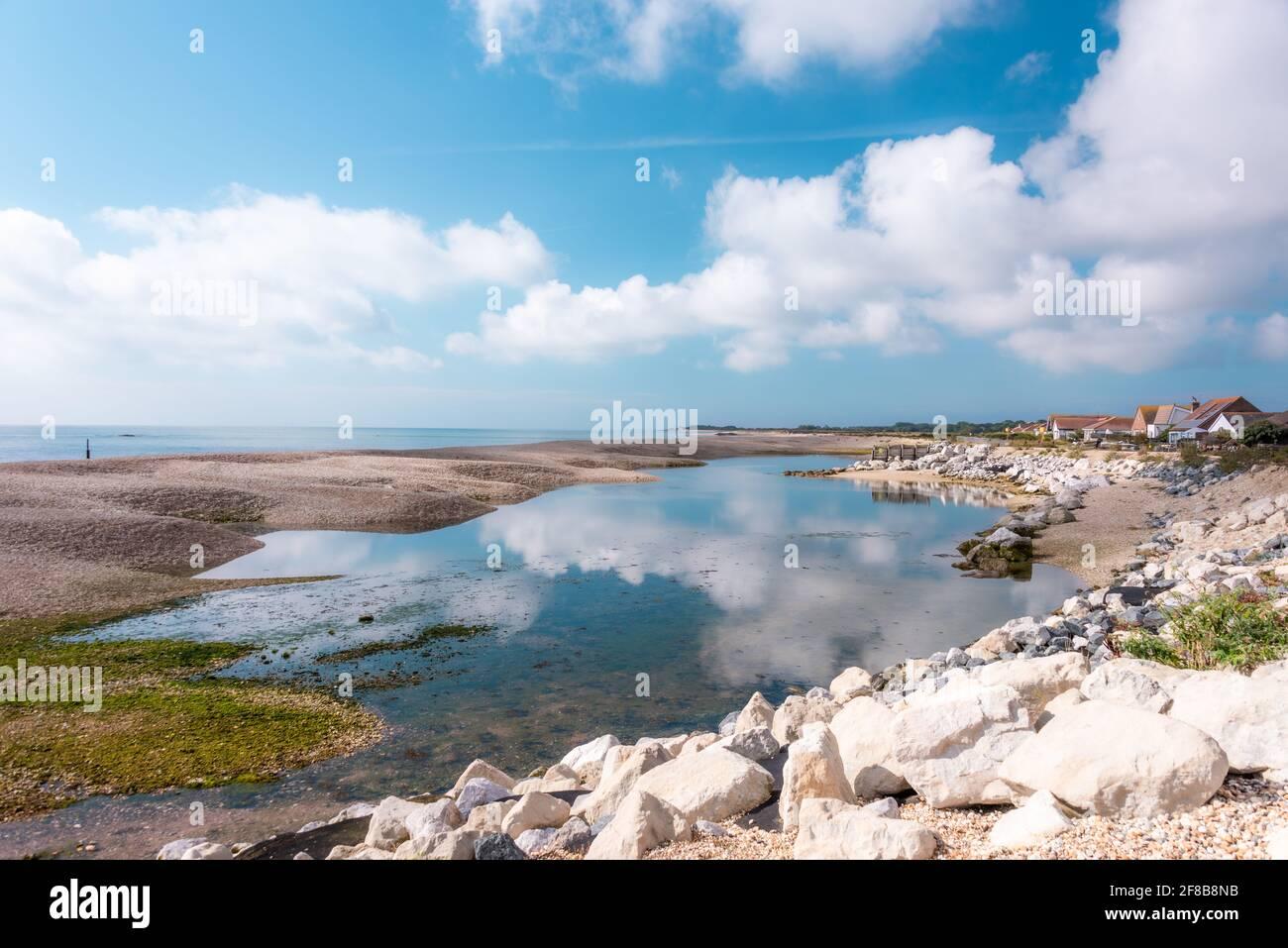 Maisons côtières avec nuages reflétés à Pagham, West Sussex. Banque D'Images