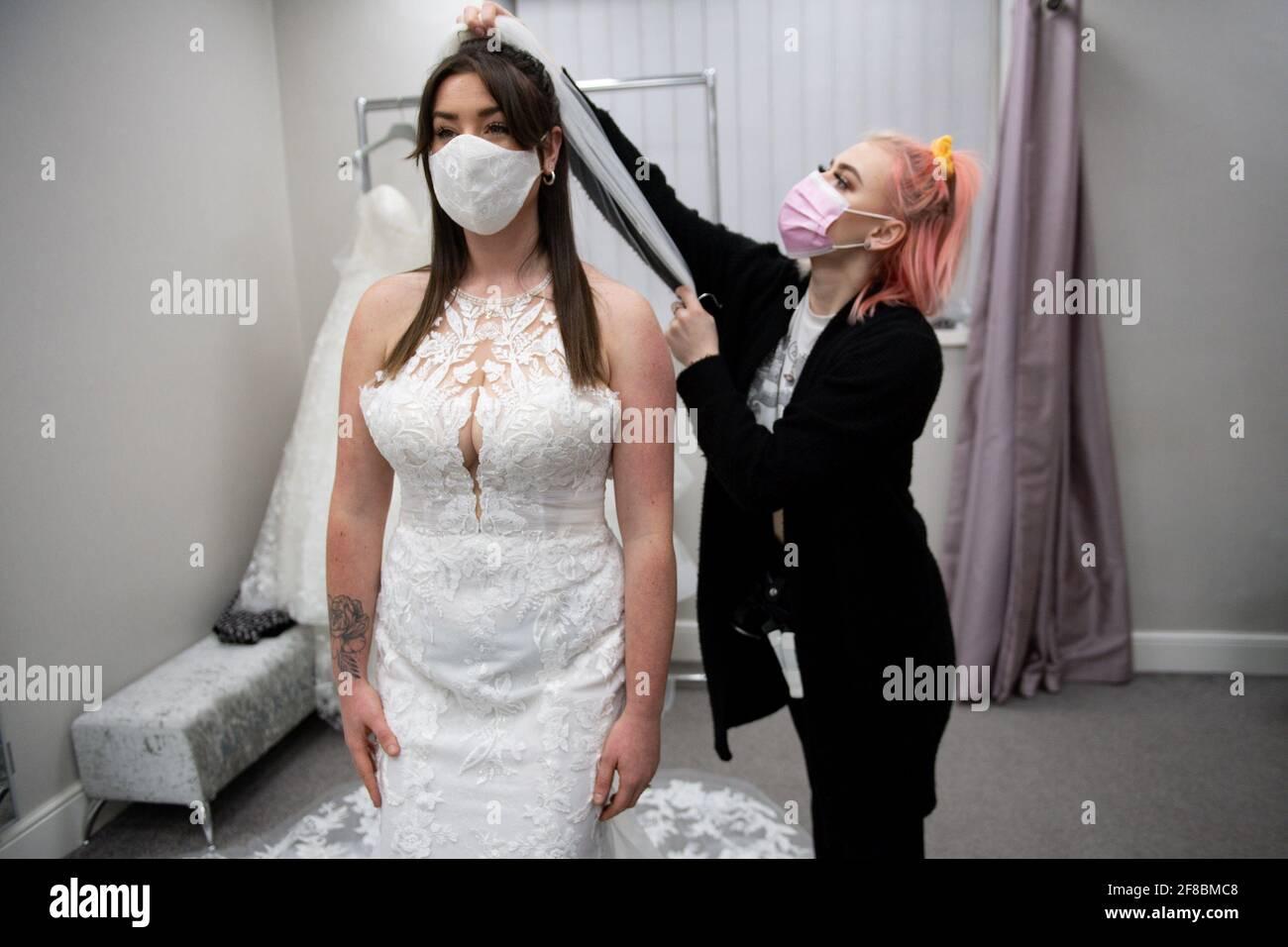 Mariée-à-être Erin Barwell tente sur des robes pour la première fois depuis que les détaillants non essentiels ont rouvert cette semaine. Erin, de Stoke-on-Trent, doit se marier en février prochain et a essayé des robes à la mariée de Roberta à Burslem, Stoke-on-Trent, suite à l'assouplissement supplémentaire des restrictions de verrouillage en Angleterre. Date de la photo: Mardi 13 avril 2021. Banque D'Images