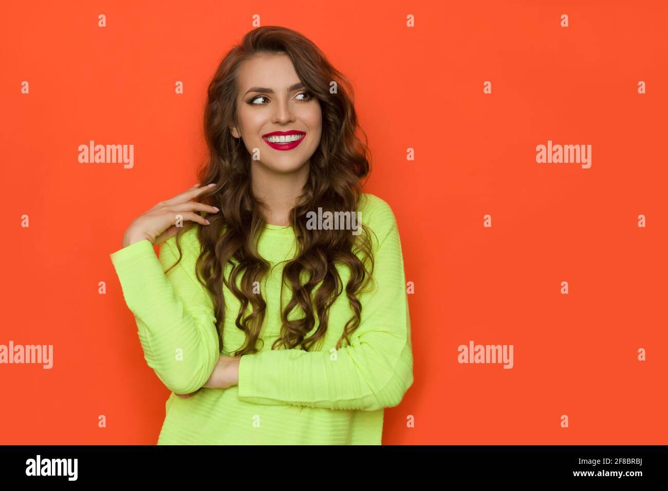 Jeune femme souriante en vert citron vert fluo regarde de côté à l'espace de copie orange. Vue avant. Prise de vue en studio à taille haute. Banque D'Images