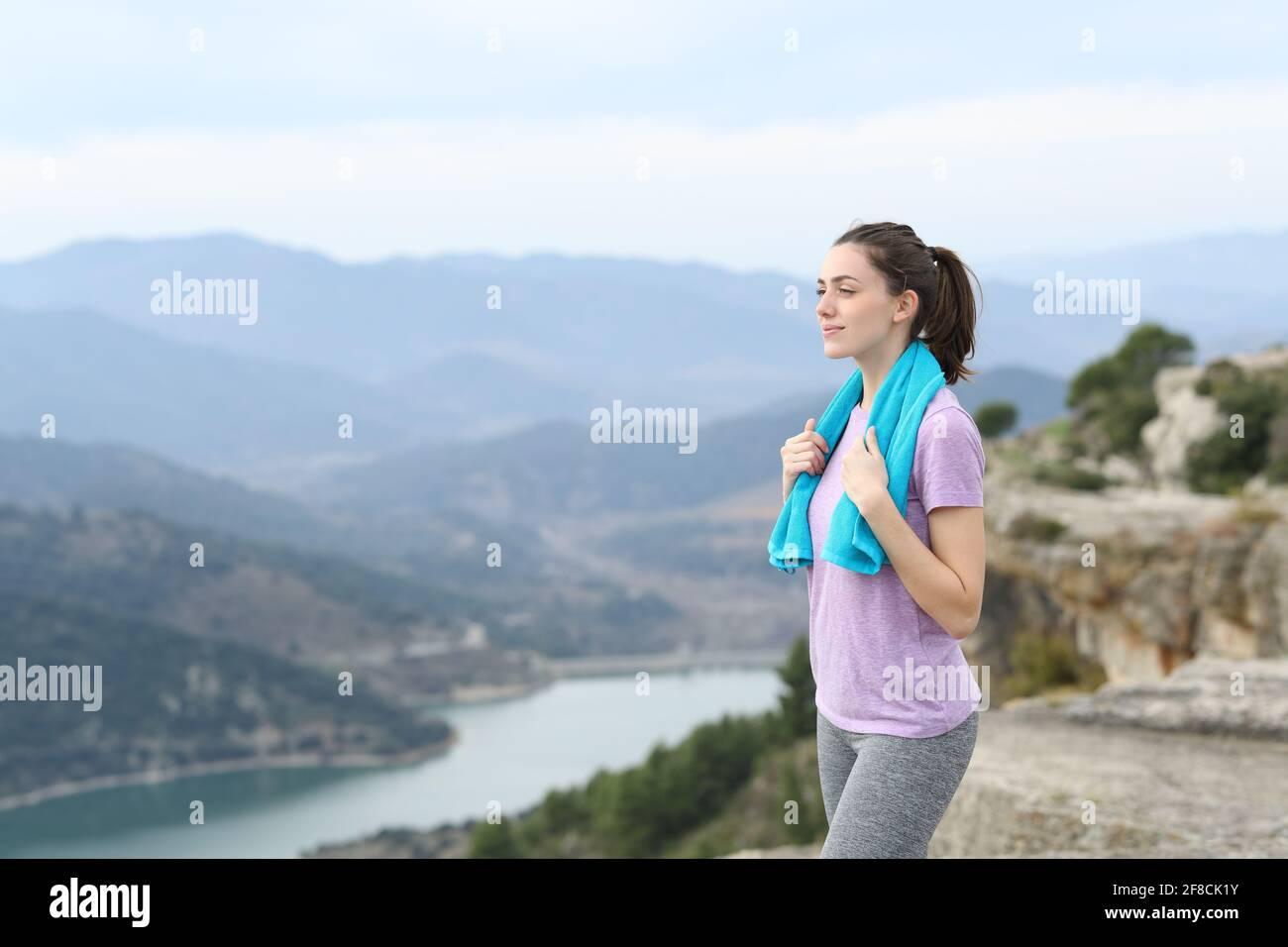Un bon coureur saisissant une serviette contemplant les vues après le sport dans le montagne Banque D'Images