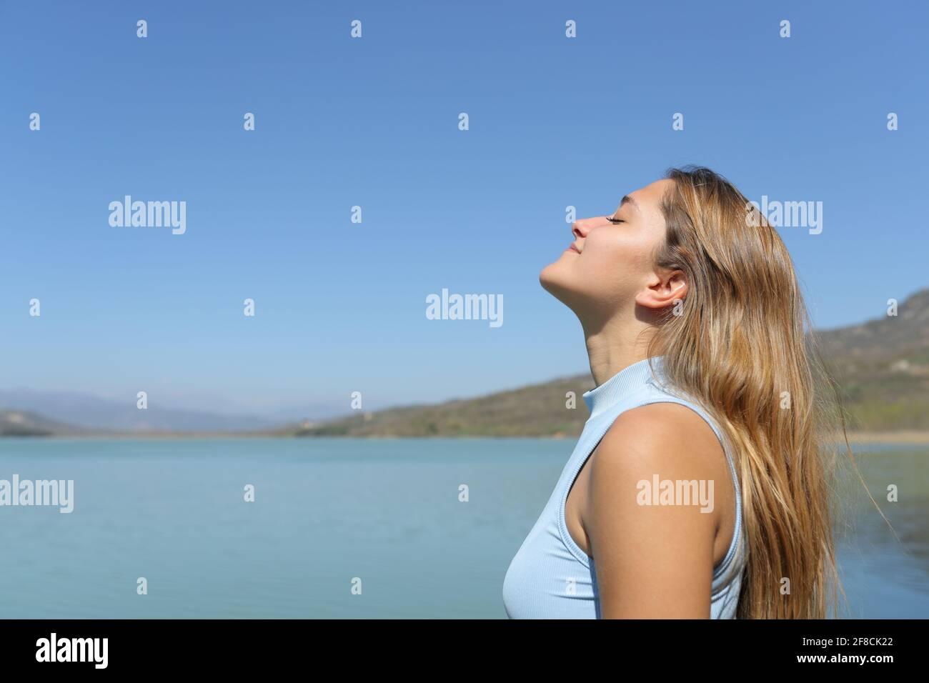 Vue latérale d'une femme détendue respirant de l'air frais dans un lac Banque D'Images