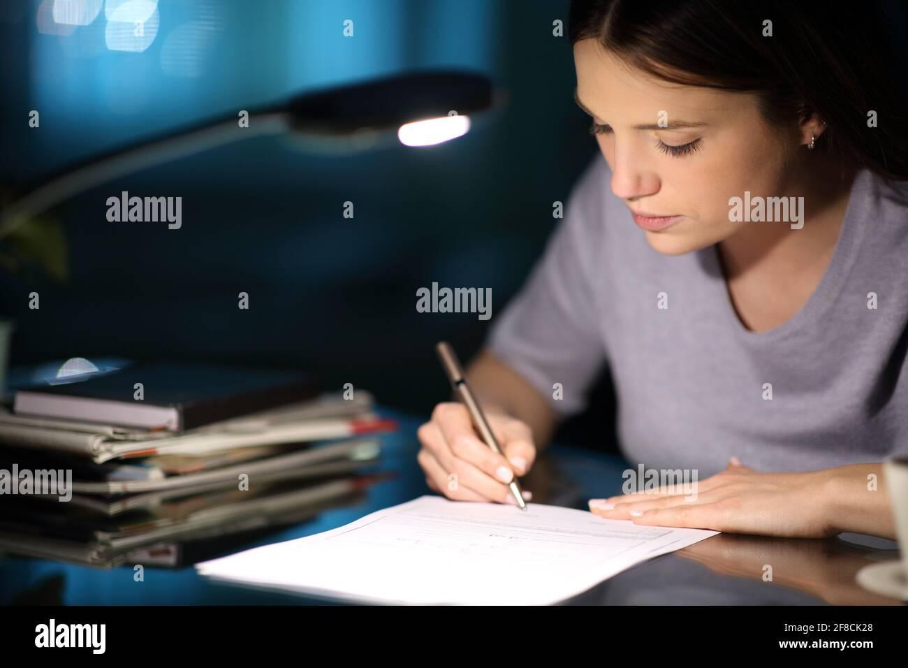 Femme sérieuse signant la forme dans la nuit à la maison Banque D'Images