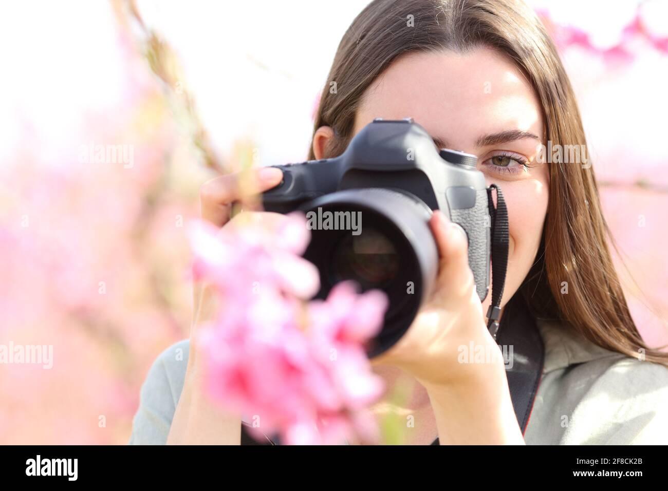 Vue avant portrait d'un photographe photographiant des fleurs avec macro objectif et appareil photo reflex numérique dans un champ Banque D'Images