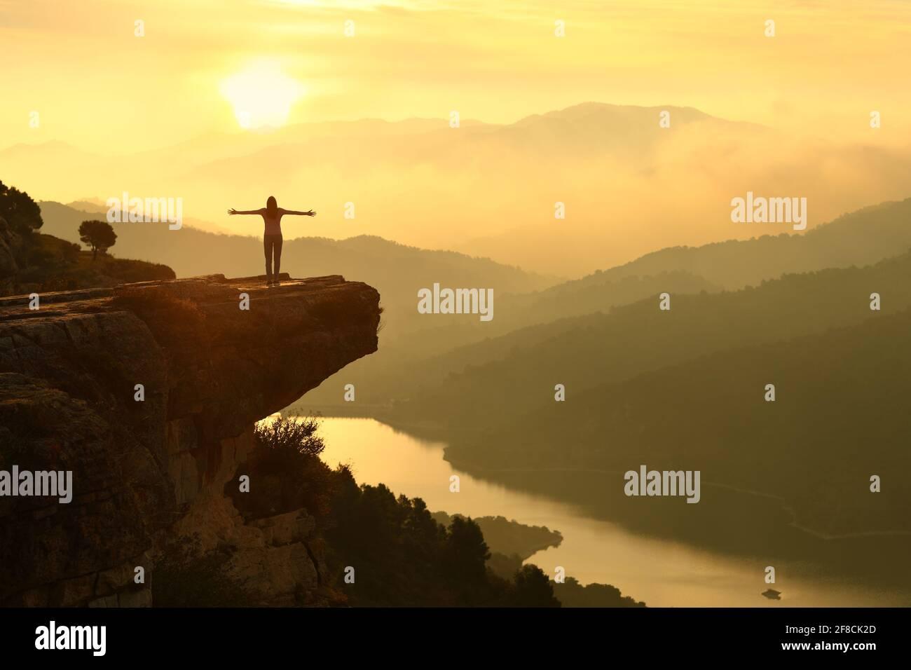 Vue arrière portrait d'une silhouette de femme célébrant le succès dans un magnifique paysage de coucher de soleil Banque D'Images