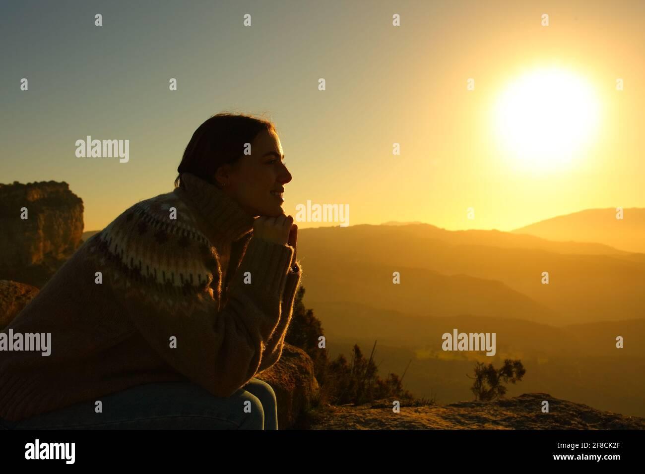 Profil de contre-jour d'une silhouette de femme méditant au coucher du soleil à l'intérieur la montagne Banque D'Images