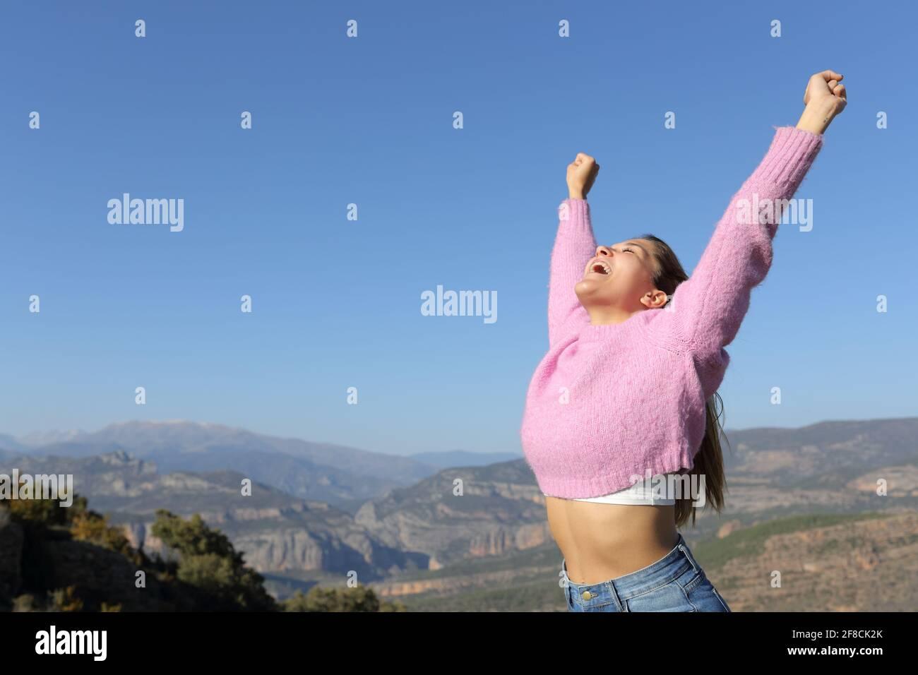 Femme excitée en rose levant des bras célébrant des vacances dans le montagne une journée ensoleillée Banque D'Images
