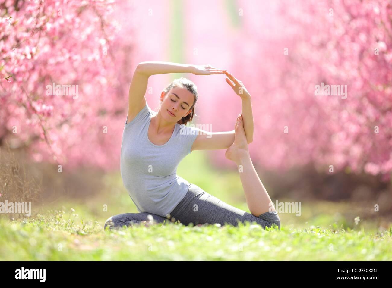 Vue de face d'un exercice de yoga yogi pratiqué dans un champ à fleurs roses Banque D'Images