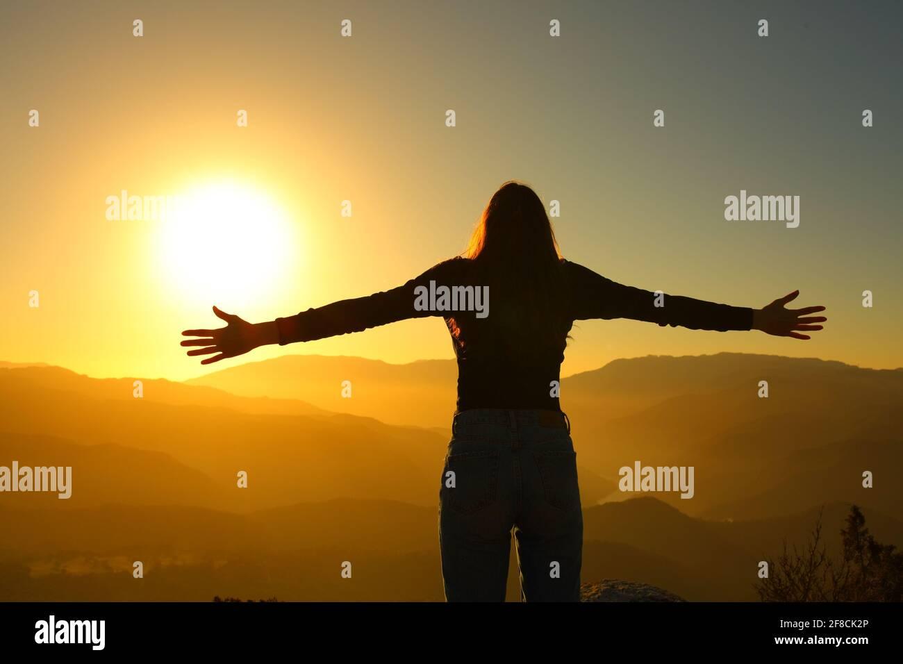 Vue arrière silhuette d'une femme se propageant à bras ouverts au coucher du soleil dans la montagne Banque D'Images