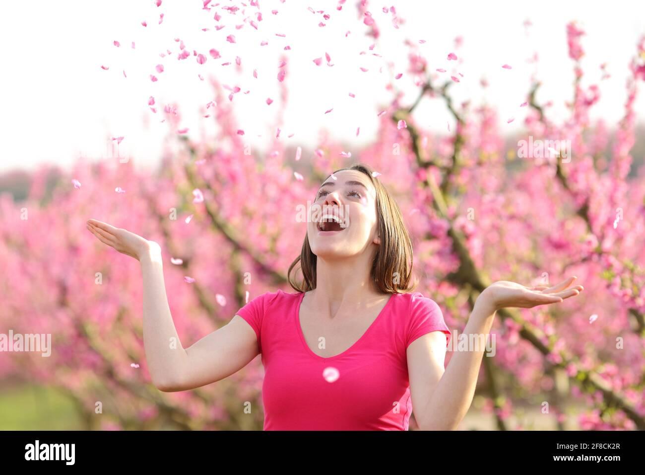 Une femme excitée jette des pétales de fleur dans l'air au printemps dans un champ rose Banque D'Images