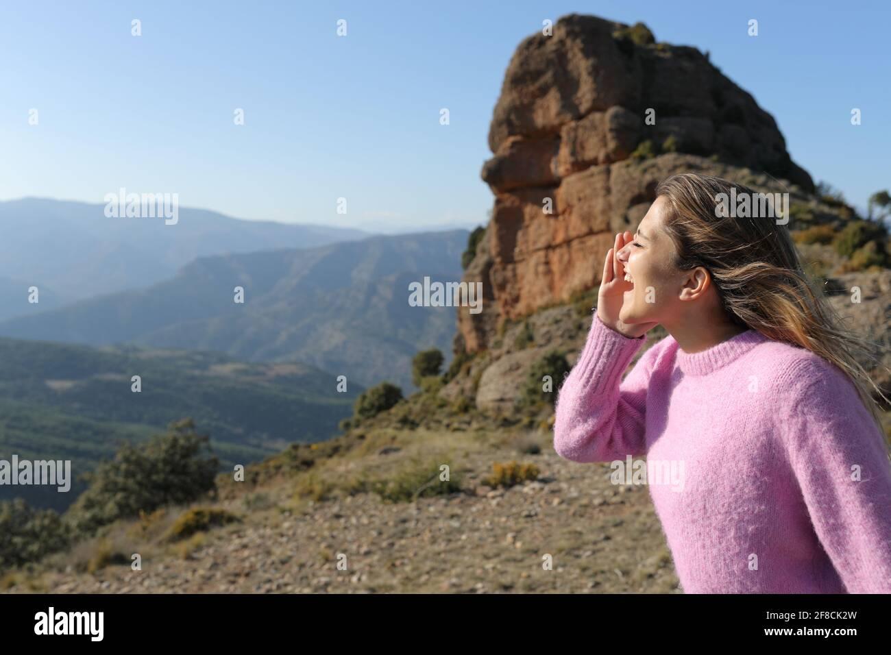 Profil d'une femme heureuse criant dans la montagne sur vacances Banque D'Images