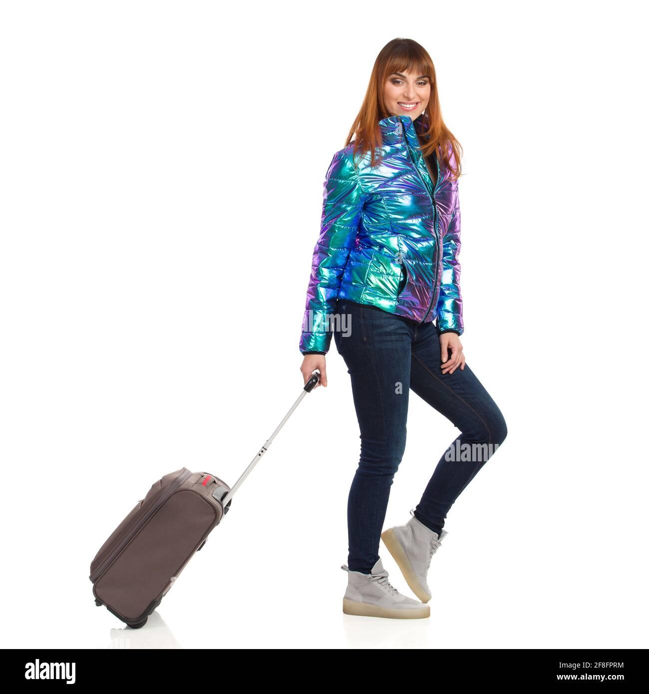 Une jeune femme en veste en duvet brillante et éclatante marche avec un sac trollay, regarde l'appareil photo et sourit. Vue latérale. Prise de vue en studio pleine longueur isolée o Banque D'Images