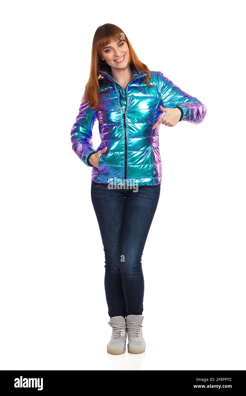 La jeune femme en veste, jeans et baskets en duvet, vibrante et brillante, se fait remarquer et sourire. Vue avant. Prise de vue en studio sur toute la longueur isolée sur W Banque D'Images