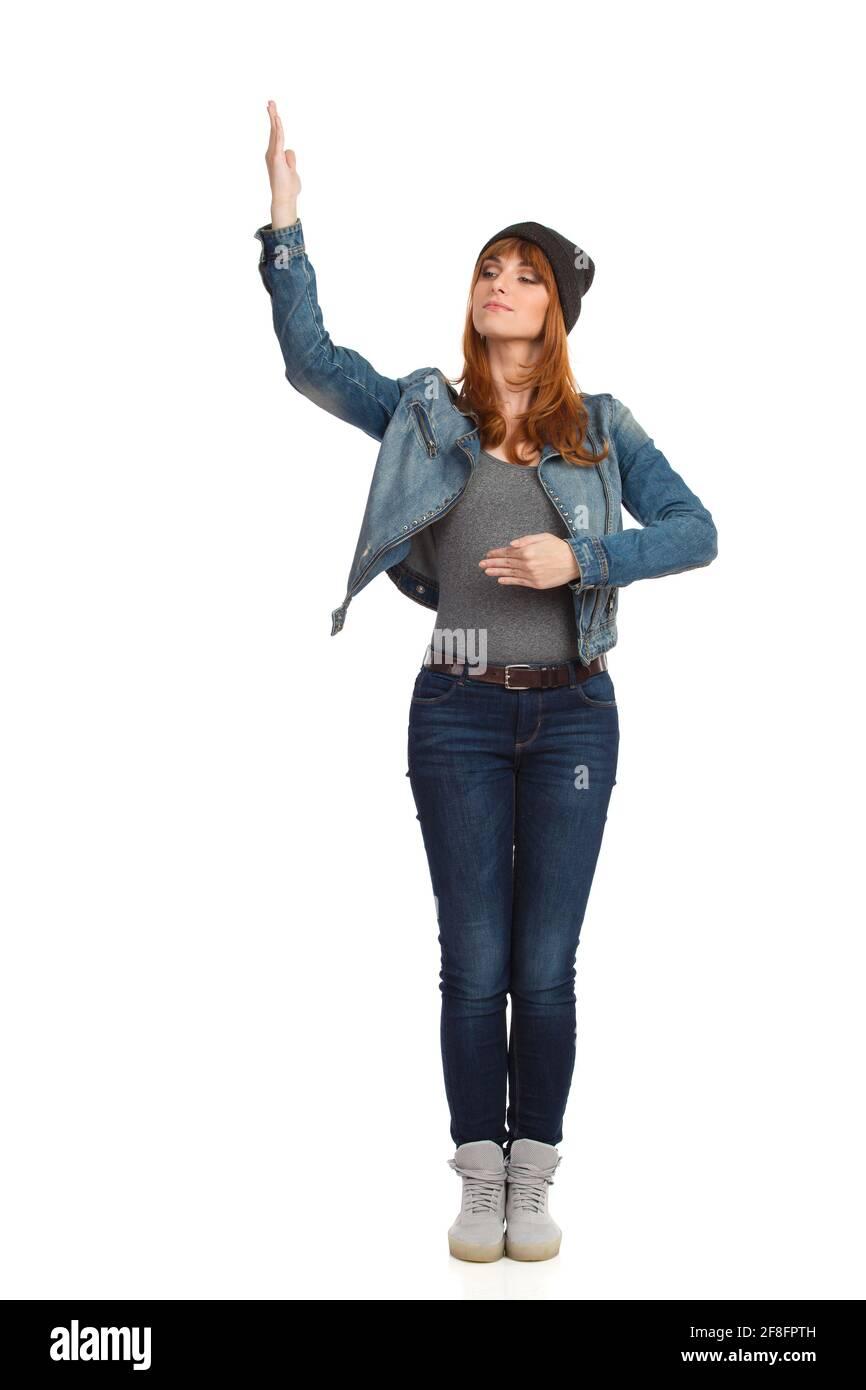 Jeune femme sérieuse en veste de Jean non boutonnée, est debout, tenant le bras relevé et regardant loin. Vue avant. Prise de vue en studio sur toute la longueur isolée sur le coup Banque D'Images